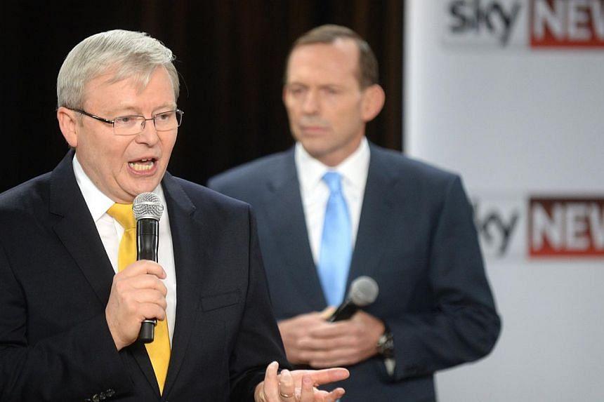 Australia's Prime Minister Kevin Rudd (left) speaks as oppostion leader Tony Abbott (right) listens during a people's forum in Brisbane on Aug 21, 2013. -- PHOTO: AFP