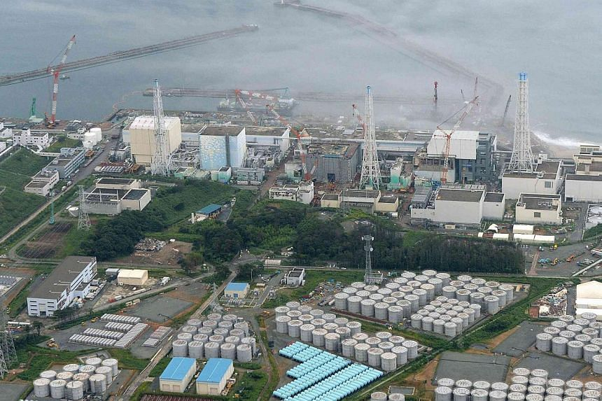 An aerial view shows Tepco's tsunami-crippled Fukushima Daiichi nuclear power plant and its contaminated water storage tanks (bottom) in Fukushima, in this photo taken by Kyodo on Aug 20, 2013. Workers at the plant scrambled to check 300 tanks storin
