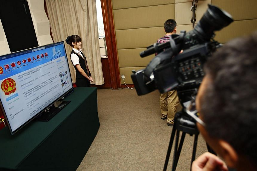 Journalists are seen next to a television screen displaying the Weibo (Chinese version of Twitter) page of Jinan Intermediate People's Court, at the media centre of the court during the trial of disgraced Chinese politician Bo Xilai in Jinan, Shandon