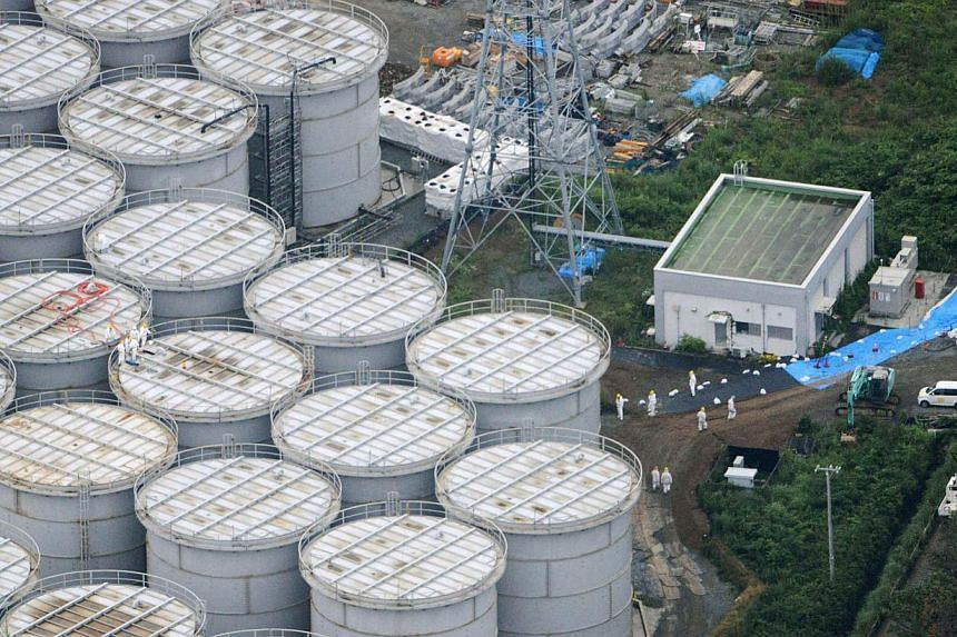 An aerial view shows workers wearing protective suits and masks working atop contaminated water storage tanks at Tokyo Electric Power Co's (Tepco) tsunami-crippled Fukushima Daiichi nuclear power plant in Fukushima, in this photo taken by Kyodo on Tu