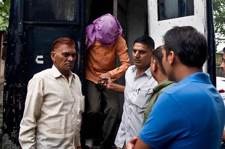 Indian policemen escort a teenager (second from left)charged over the fatal gang-rape of a student last Decemberfrom a police vehicle outside the juvenile court in New Delhi on Monday, Aug 19, 2013. India's Supreme Court cleared the way o