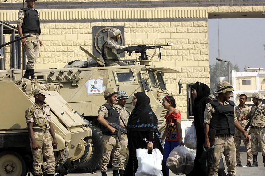 Women walk past soldiers guarding Torah prison, where Egypt's deposed autocrat president Hosni Mubarak is held, in Cairo, Egypt on Thursday, Aug 22, 2013. Egypt's state prosecutor on Thursday cleared ousted Mr Mubarak for conditional release from pri