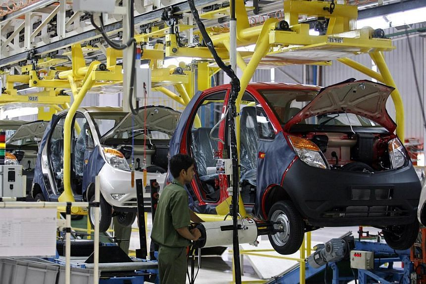"An employee works inside the newly inaugurated plant for the Tata Nano car at Sanand in the western Indian state of Gujarat on June 2, 2010. India's top vehicle maker Tata Motors says it plans to reposition the Nano as a ""smart city car"" after its ma"