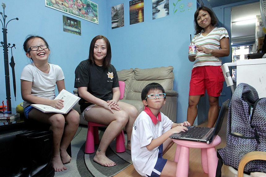 Administrative assistant Angela Zeng (in black) with her daughter Valerie, son Javier and helper Kuswinarsih in their home - a two-room flat in Toa Payoh. They are among families who stand to gain from the new grant for HDB upgraders announced by PM