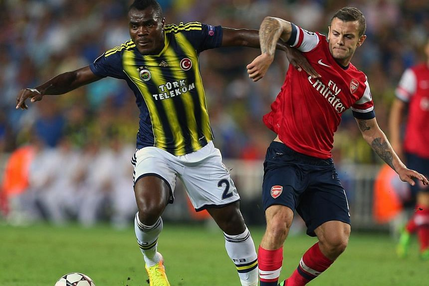 Fenerbahce's Emmanuel Emenike, right, vies with Jack Wilshere of Arsenal for the ball during their Champions League qualifying playoffs, first leg soccer match at Sukru Saracoglu Stadium in Istanbul, Turkey, on Wednesday, Aug 21, 2013.