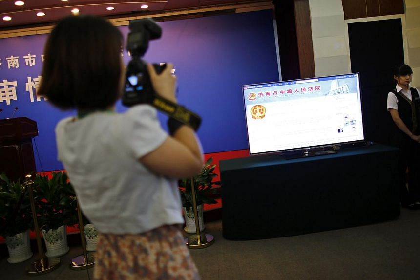 A journalist takes pictures near a television screen displaying the Weibo (Chinese version of Twitter) page of Jinan Intermediate People's Court, at the media centre of the court during the trial of disgraced Chinese politician Bo Xilai in Jinan, Sha