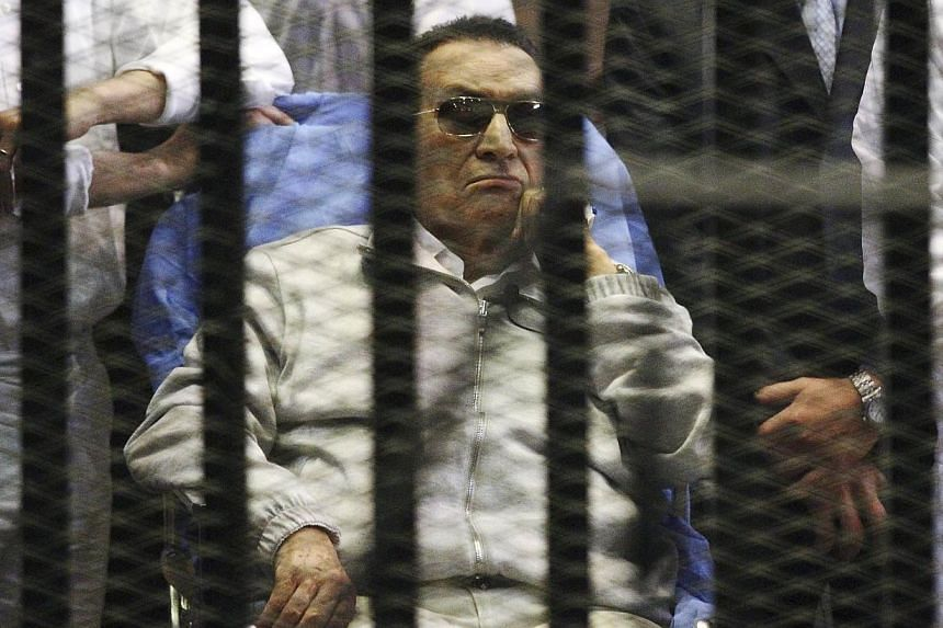 Egypt's ousted President Hosni Mubarak sits inside a dock at the police academy on the outskirts of Cairo in this April 15, 2013 file photo. Egypt's military on Wednesday ordered Mubarak to be placed under house arrest, as the former president appear