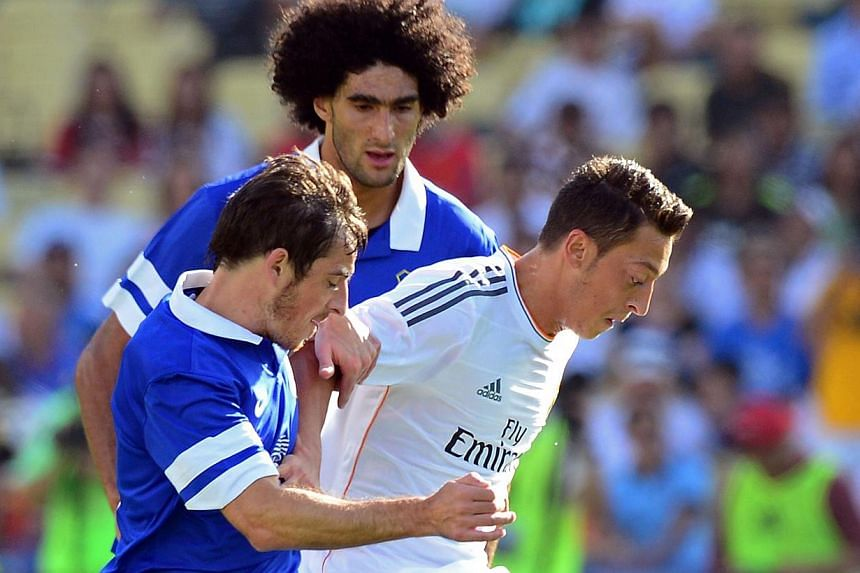 (From left) Everton'sLeighton Baines and Marouane Fellainitussle with Real Madrid's Mesut Oezilduring a pre-season friendly on Aug 3, 2013. Everton manager Roberto Martinez says they have not received further bids from Manchester Un