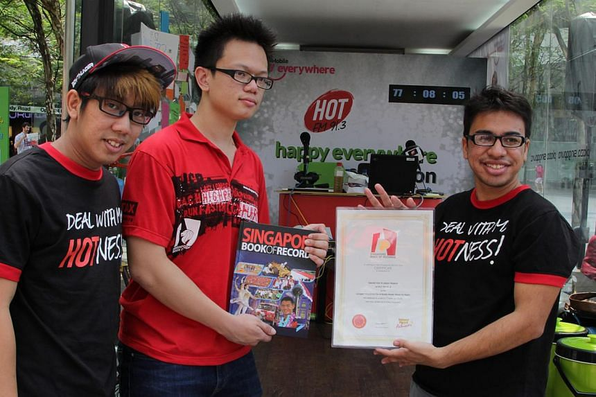 Hot FM91.3 DJs Boy Thunder (left) and Adam Piperdy (right) receive their certificates from a representative of the Singapore Book of Records for their radio marathon on Saturday, March 23, 2013. It was confirmed on Friday, Aug 23, 2013, that the two