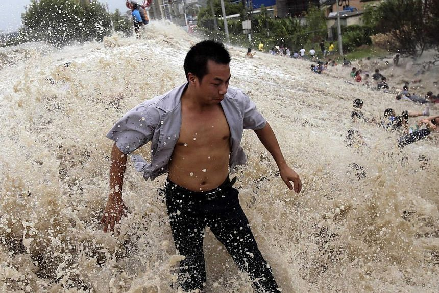 People struggle as waves from a tidal bore surge past a barrier on the banks of Qiantang River in Haining, Zhejiang province on Thursday, Aug 22, 2013. See more pictures from around the world in Through The Lens' Today in Pictures. -- PHOTO: REU