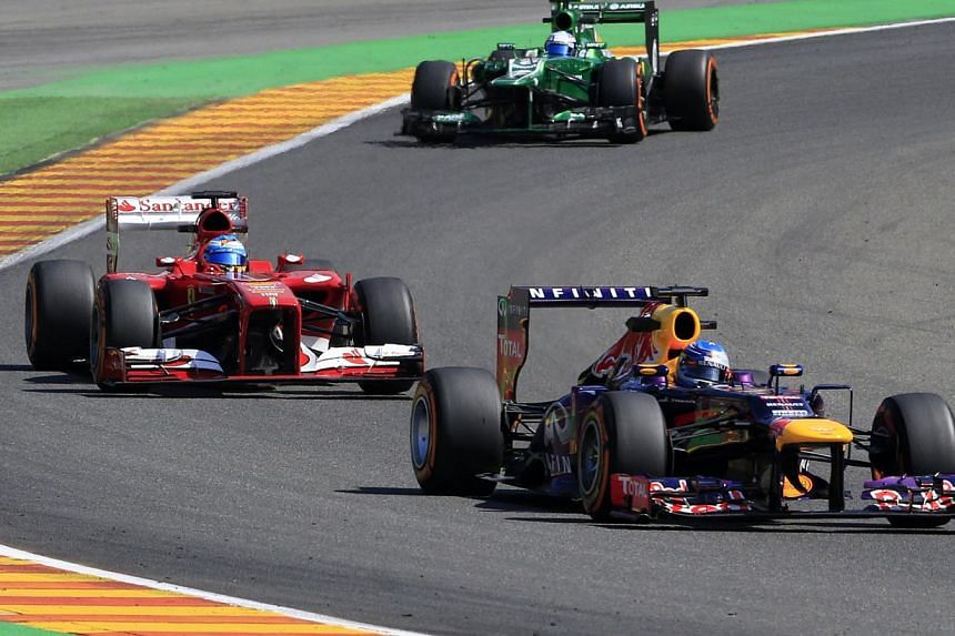Ferrari's Spanish driver Fernando Alonso, Caterham F1 Team's Dutch driver Guido Van Der Garde and Red Bull Racing's German driver Sebastian Vettel drive during the second practice session at the Spa-Francorchamps circuit in Spa on Aug 23, 2013 ahead