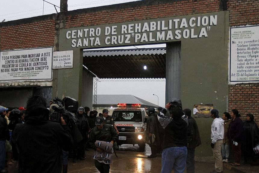 Relatives of inmates wait for news at the entrance of Palmasola prison in the outskirts of Santa Cruz on Friday, Aug 23, 2013.A young child was among the 30 people killed on Friday when a fight broke out between rival gangs at the overpopulated