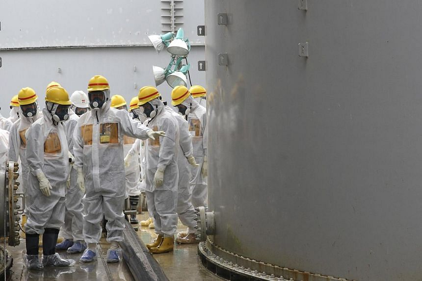 Japan's Nuclear Regulation Authority (NRA) member Toyoshi Fuketa (centre) and other members wearing protective suits and masks inspect contaminated water tanks at the tsunami-crippled Fukushima nuclear power plant on Friday, Aug 23, 2013.Fukush