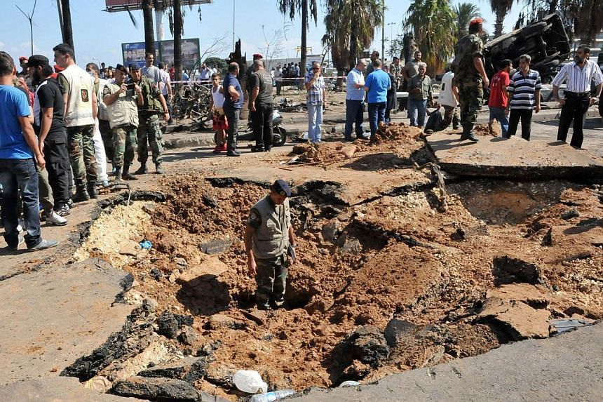 Lebanese soldiers inspect on Saturday, Aug 24, 2013, the crater left by a bombing outside Al-Taqwa mosque in the northern city of Tripoli. Al-Qaeda's North African branch blamed Lebanese Shi'ite Muslim militant group Hizbollah for twin bombs that hit