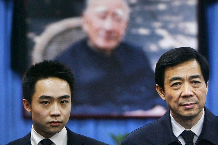Fallen Chinese politician Bo Xilai(right), seen with his son Bo Guagua,stands in front of a picture of his father Bo Yiboat a mourning hall in Beijing on Jan 18, 2007. No tidbit in Bo's trial has attracted as much attention as the p