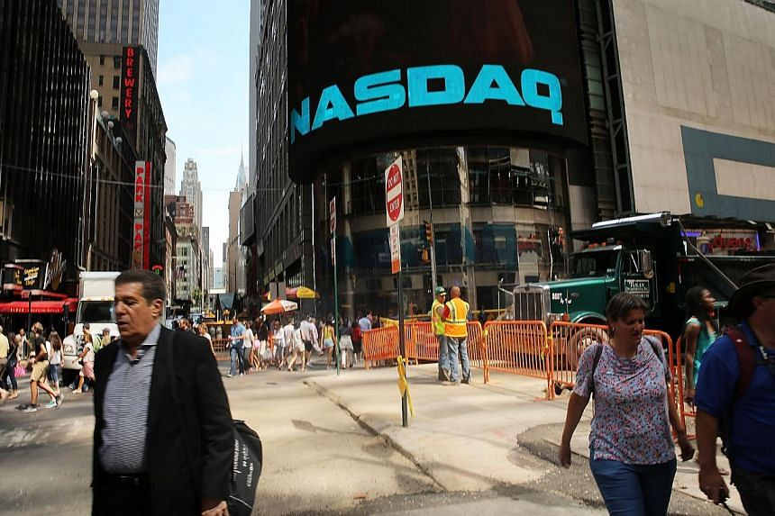 People walk by the Nasdaq stock market one day after the the electronic exchange experienced a a three-hour trading delay due to a technical problem on Aug 23, 2013 in New York City. -- PHOTO: AFP