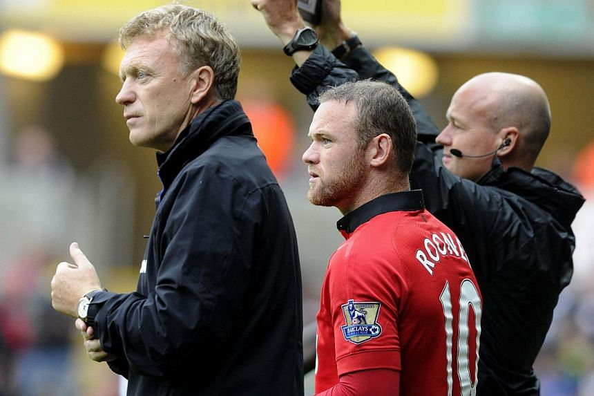 Manchester United's manager David Moyes (left) waits with Wayne Rooney to come onto the pitch as a substitute against Swansea City, during their English Premier League soccer match at Liberty Stadium, Swansea, Aug 17, 2013. -- FILE PHOTO: REUTERS