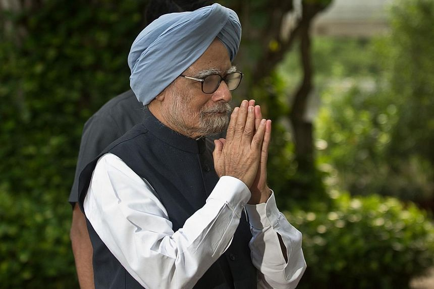 In this photograph taken on July 30, 2013, Indian Prime Minister Manmohan Singh gestures as he arrives for the Congress Working Committee meeting with other Congress leaders in New Delhi. India's embattled prime minister appealed on August 24, 2013 t