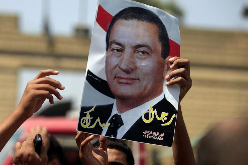 A supporter of Egypt's deposed autocrat Hosni Mubarak holds a poster of him and chants slogans in front of Tora prison, where Mubarak has been held, in Cairo, on Thursday, Aug 22, 2013.Egypt's former president Hosni Mubarak returns to court on