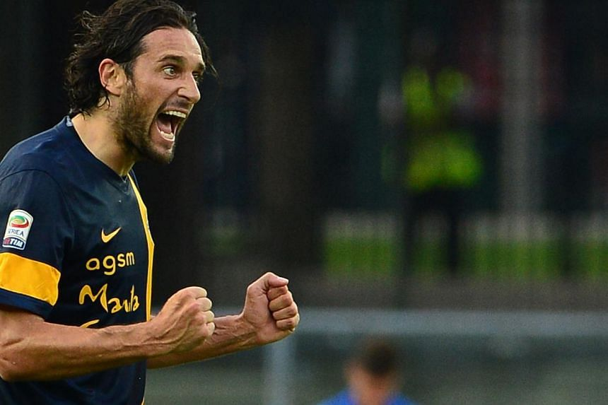 Hellas Verona's forward Luca Toni celebrates with teammates after scoring a goal during the Serie A football match Hellas Verona vs. AC Milan at Bentegodi Stadium in Verona on August 24, 2013. Veteran striker Luca Toni scored twice in a shock 2-1 hom