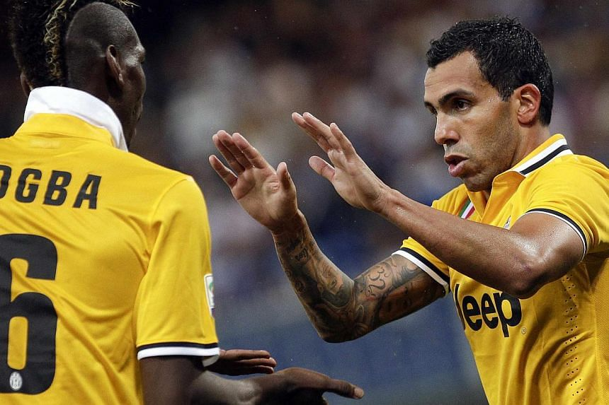 Juventus' Carlos Alberto Tevez (right) celebrates with Paul Labile Pogba (left) after scoring against Sampdoria during their Italian Serie A soccer match in Genova, on Aug 24, 2013. Argentine striker Carlos Tevez scored on his Serie A debut for Juven