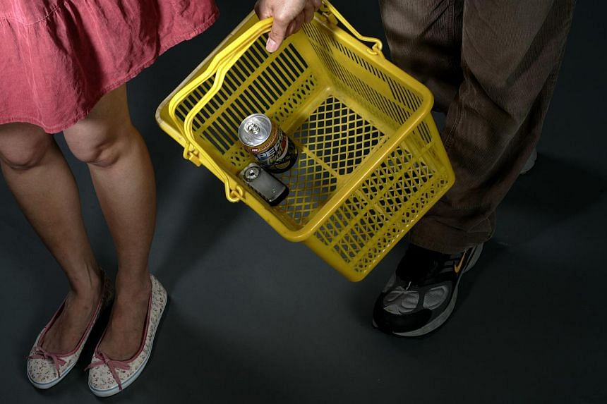 """Posed photo of a man holding a supermarket basket with a mobile phone in it. A recent spate of cases involving men who filmed """"upskirt videos"""" of women in public places prompted a judge to ask if this crime is on the rise.-- ST FILE PHOTO: WANG"""