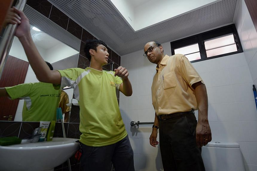 Deputy Prime Minister Tharman Shanmugaratnam inspects railings installed by ITE College West student, Muhammad Ridwanbin Abdul Rais (left), and his coursemates in the washroom of a lower middle-income family during the launch of the Adopt-A-Precinct