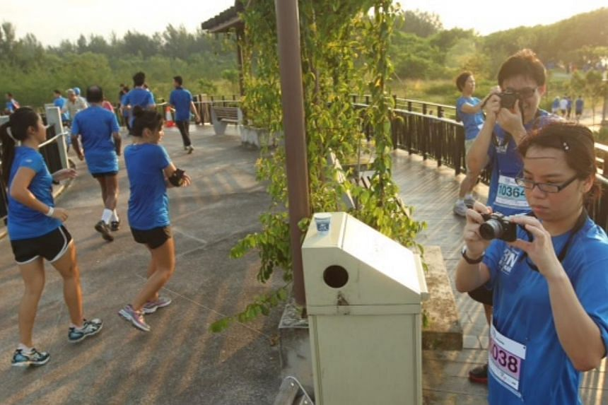 Runners stop to take photographs at the sunrise bridge along Punggol Waterway at The Straits Times Run In The Park 2013. -- ST PHOTO: SEAH KWANG PENG