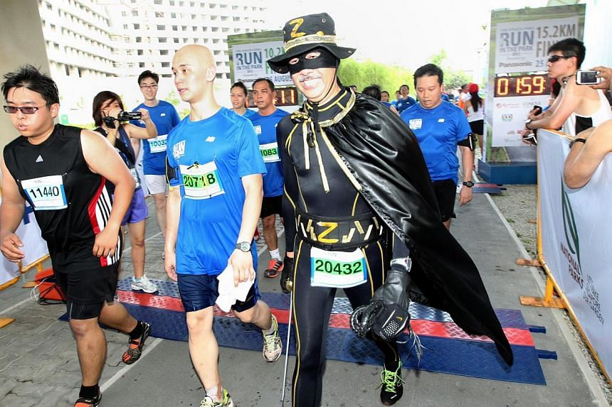 A man dressed as Zorro crosses the finishing line at The Straits Times' Run in the Park held at Punggol Waterway on Aug 25, 2013. -- ST PHOTO: NEO XIAOBIN