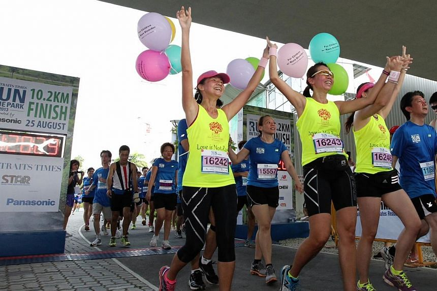 Participants hold hands as they cross the finishing line at The Straits Times' Run in the Park held at Punggol Waterway on Aug 25, 2013. -- ST PHOTO: NEO XIAOBIN