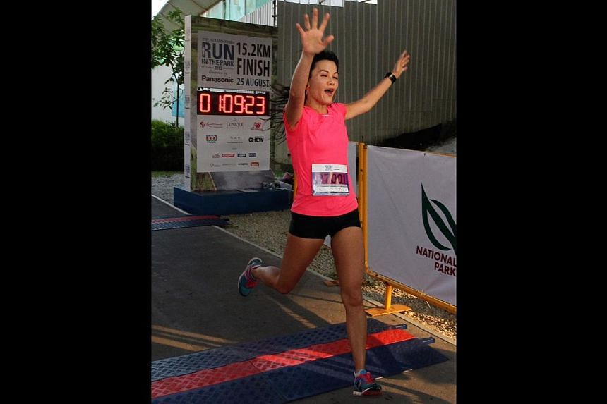 Jenny Huang, 40, winner of the 15km (Women) category at The Straits Times' Run in the Park held at Punggol Waterway on Aug 25, 2013. -- ST PHOTO: NEO XIAOBIN