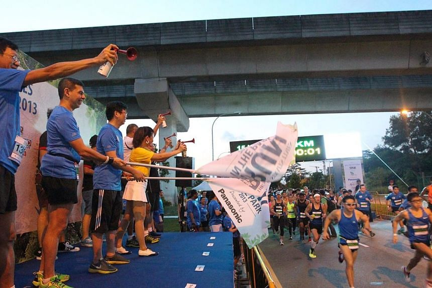 The Straits Times editor Warren Fernandez (second from left) flags off participants of the 15km category at The Straits Times' Run in the Park held at Punggol Waterway on Aug 25, 2013. -- ST PHOTO: NEO XIAOBIN