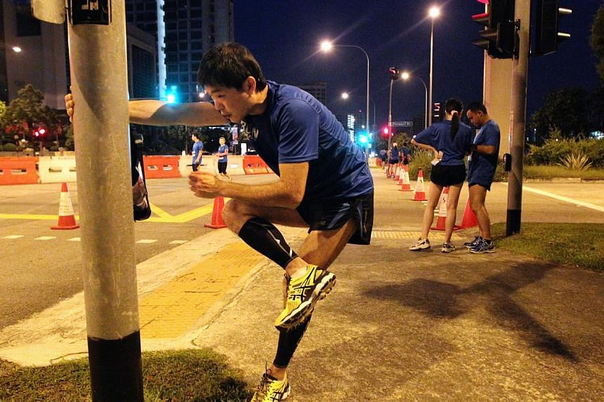 Participants of The Straits Times' Run in the Park warm up before the start of the race held at Punggol Waterway on Aug 25, 2013. -- ST PHOTO: NEO XIAOBIN