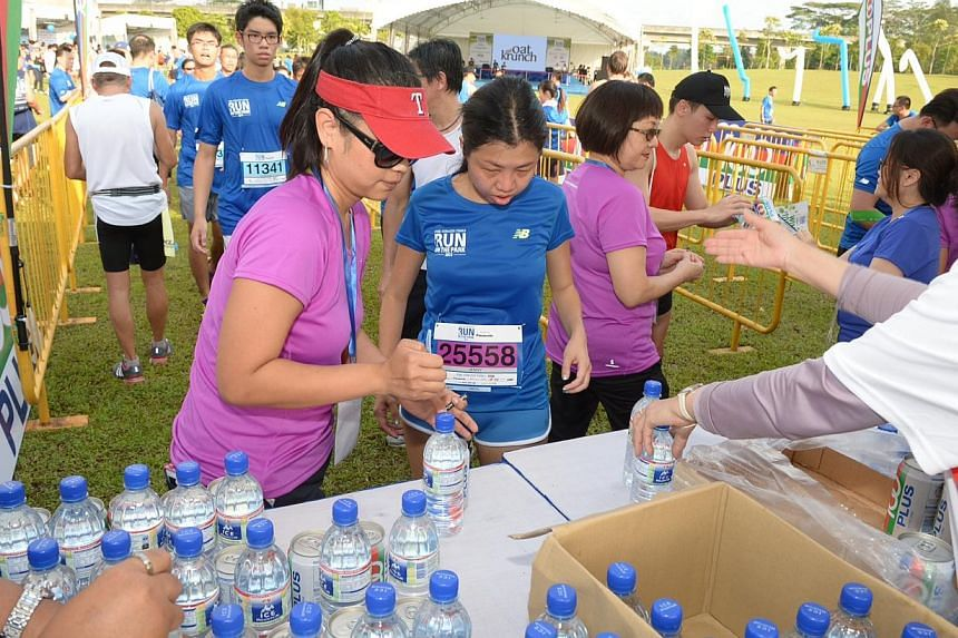 Runners collect their goodie bags at the collection point at the post-race carnival. -- ST PHOTO: DESMOND WEE