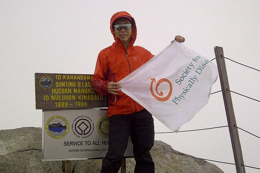 Mr David Lim, 49, flying the Society for the Physically Disabled (SPD) flag when he reached Mount Kinabalu's rocky top, as he had on previous climbs. His non-stop attempt on Friday was to raise funds for the SPD.