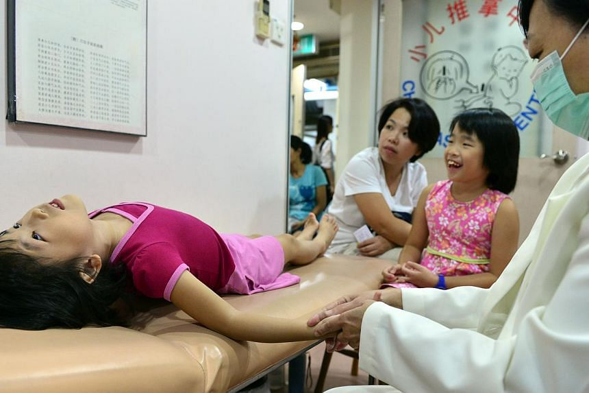 Ellie Lee, six, receiving treatment (above) at Yu Guo under the watchful eye of her mum and sister. The clinic is usually crowded with parents and children on weekday nights. -- ST PHOTOS: DESMOND FOO