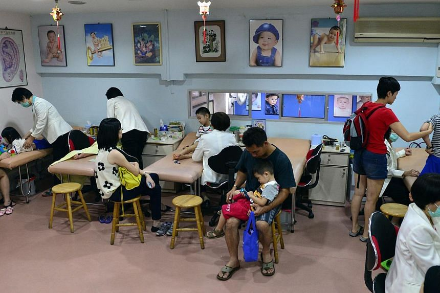 Ellie Lee, six, receiving treatment at Yu Guo under the watchful eye of her mum and sister. The clinic is usually crowded (above) with parents and children on weekday nights. -- ST PHOTOS: DESMOND FOO
