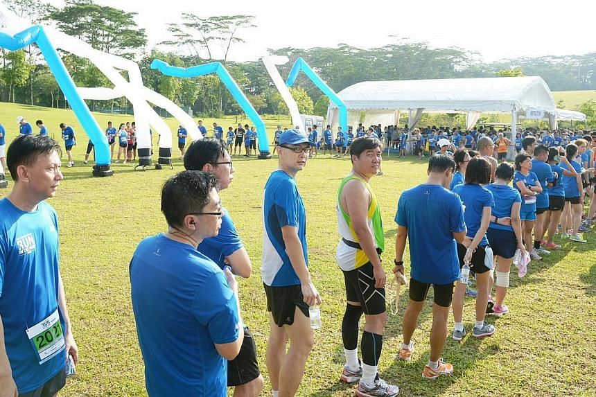 Runners wait to collect their medals at Punggol Waterway on Sunday, Aug 25, 2013. -- ST PHOTO: DESMOND WEE