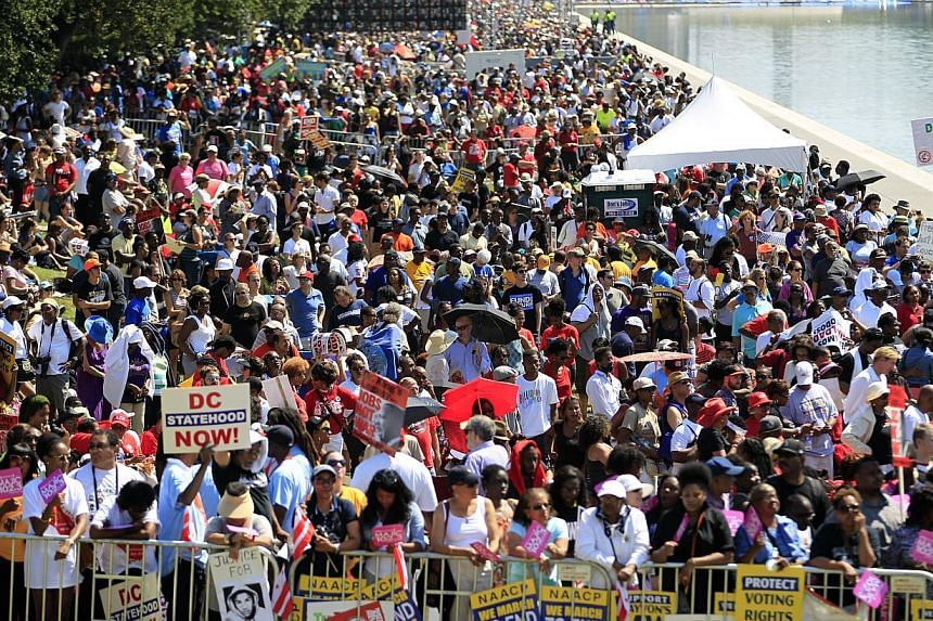 People line the reflecting pool as they listen to speakers at a rally to commemorate the 50th anniversary of the 1963 March on Washington on Saturday, Aug 24, 2013, in Washington. Tens of thousands of people marched to the Martin Luther King Jr. Memo
