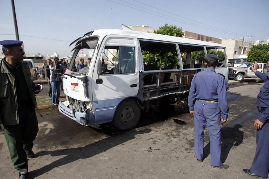 A policeman (left) and air force officers gather at the site of a bomb attack on a military bus in Sanaa on Sunday, Aug 25, 2013. At least six people were killed and 26 wounded on Sunday in the bomb attack on the bus carrying members of Yemen's air f