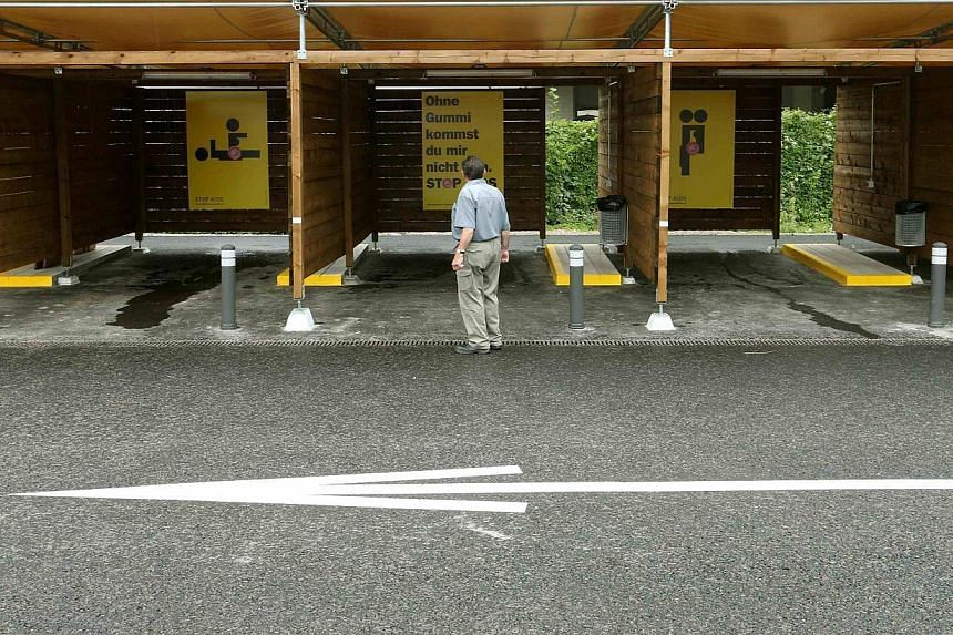 """A man standing in front of a so-called """"sex box"""" during a tour on an open day at a sex drive-in, west of Zurich on August 24, 2013. A year after voters backed the plan to ban street street walkers from the city centre in a bid to make prostitution sa"""