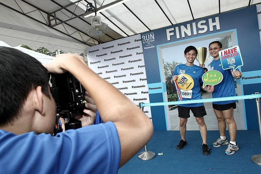 (From left) Kelvin Soh, 31, sales support manager, with Choo Choon Teck, 44, sales manager, taking pictures at the Panasonic photo booth after the race. -- ST PHOTO:  WANG HUI FEN