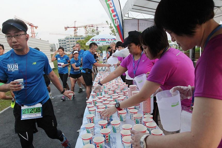 15km runners at the water point near the sunrise bridge. -- ST PHOTO: SEAH KWANG PENG