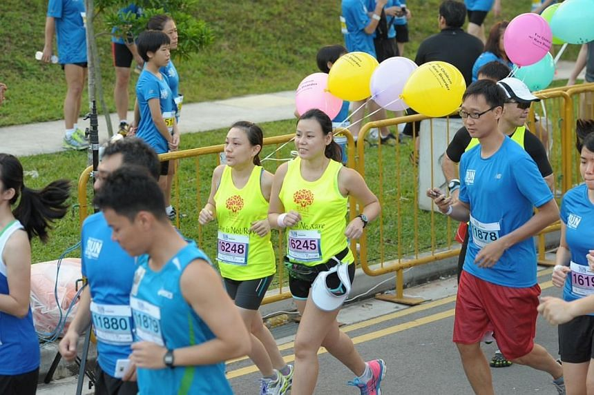 Two runners in yellow top running with balloons from Rare Disorders Society Singapore at the 10km race. Spirits were high this morning as the inaugural ST Run in the Park got underway under clear skies at the Punggol Waterway Park. -- ST PHOTO: