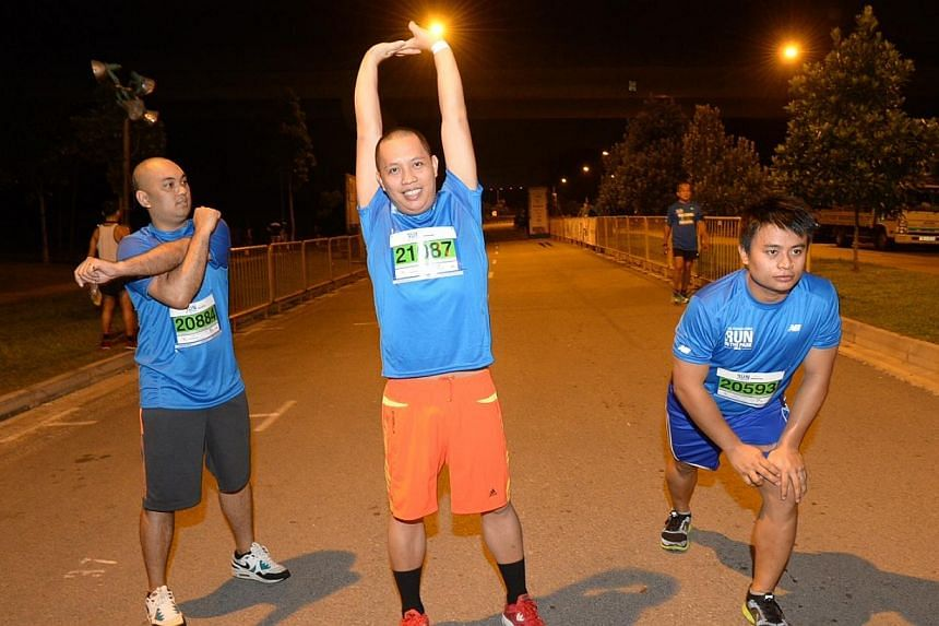 15km runners from left to right: Maynard Dioquino,29; Joseph Salvador,28 and Jerome Adriosula,26 warming up near the staring point at 6am on Sunday, Aug 25, 2013. -- ST PHOTO: DESMOND WEE