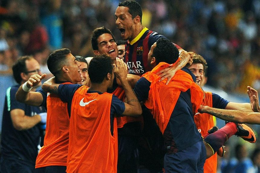 Barcelona's Brazilian defender Adriano (Top) celebrates with teammates after scoring during the Spanish league football match Malaga CF vs FC Barcelona at Rosaleda stadium in Malaga on August 25, 2013. Adriano scored the only goal as a Barcelona side