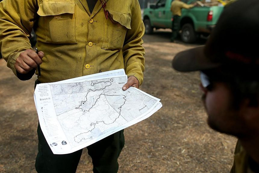 US Forest Service firefighters look at an incident map as they take a break from battling the Rim Fire at Camp Mather on Aug 25, 2013 near Groveland, California. The Rim Fire continues to burn out of control and threatens 4,500 homes outside of Yosem