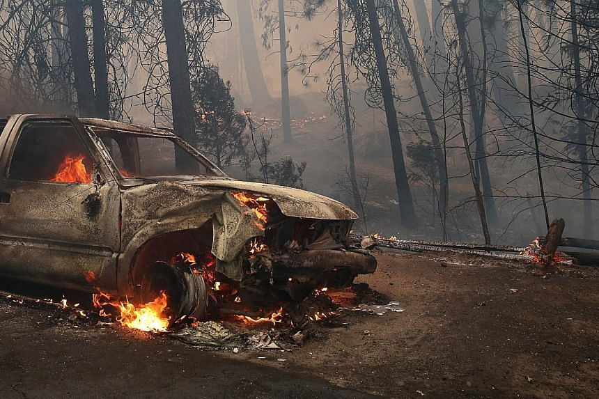 A burned car sits on the side of the road after being consumed by the Rim Fire on Aug 25, 2013 near Groveland, California. The Rim Fire continues to burn out of control and threatens 4,500 homes outside of Yosemite National Park. Over 2,000 firefight