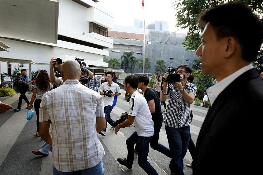Reporters run to take photos of City Harvest Church founder Kong Hee as he arrives at the Subordinate Courts on Monday, Aug 26. Kong Hee and five other leaders of the church are accused of embezzling more than $50 million from their parish to fund th