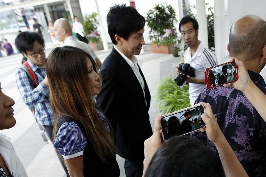 Kong Hee, founder of City Harvest Church, arrives at the Subordinate Courts with wife Ho Yeow Sun on Monday, Aug 26, 2013. He and five other leaders of the church are accused of embezzling more than $50 million from their parish to fund the secular p